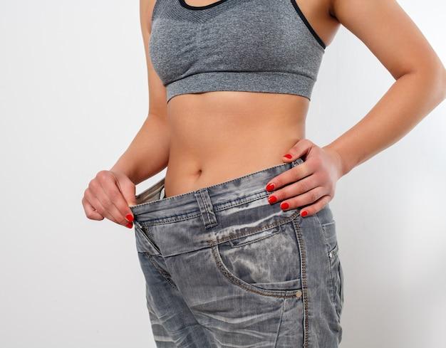 Mujer después de perder peso en jeans grandes y viejos. aislado sobre fondo blanco.