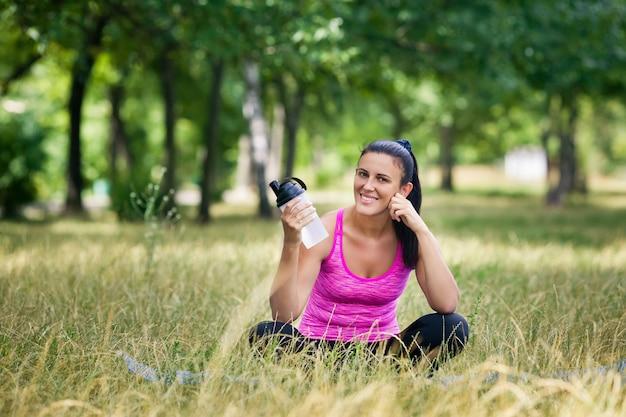 Mujer después de yoga sentado en la hierba sonriendo