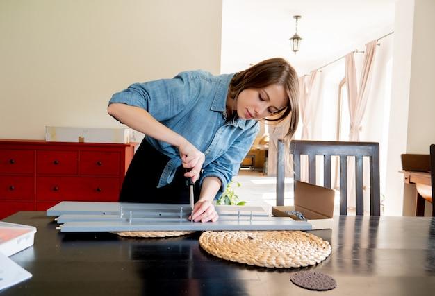 Mujer con destornillador instalando un mueble en casa personalmente