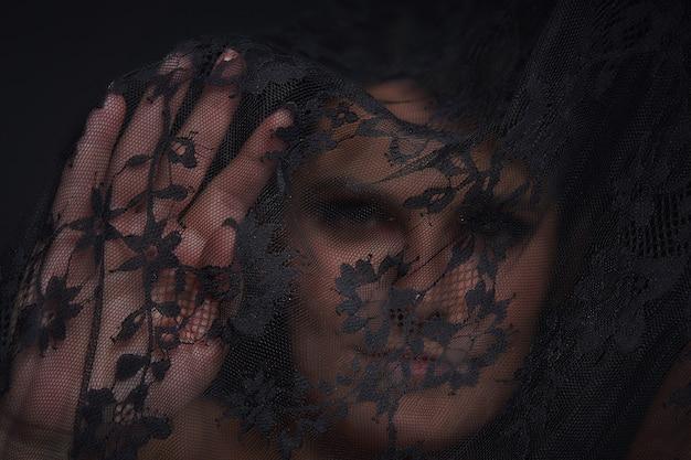 La mujer detrás de la cortina se enfoca en la palma abierta de la cara de la niña fuera de foco