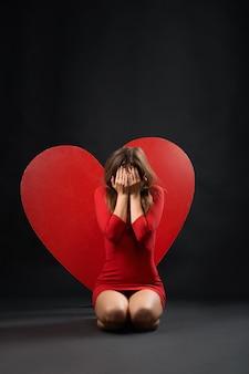 Mujer devastada llorando corazón rojo