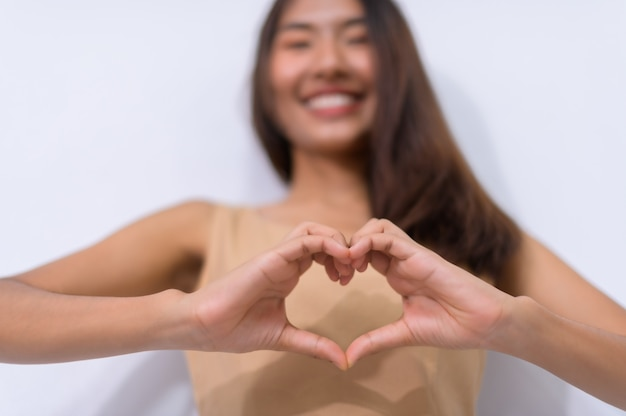 Mujer del día mundial del corazón haciendo sus manos en forma de corazón