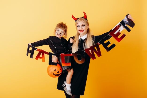 Mujer del diablo de pie contra un amarillo con una niña y sosteniendo una postal de halloween