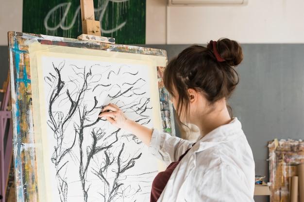 Mujer dibujando con carboncillo sobre lienzo en taller