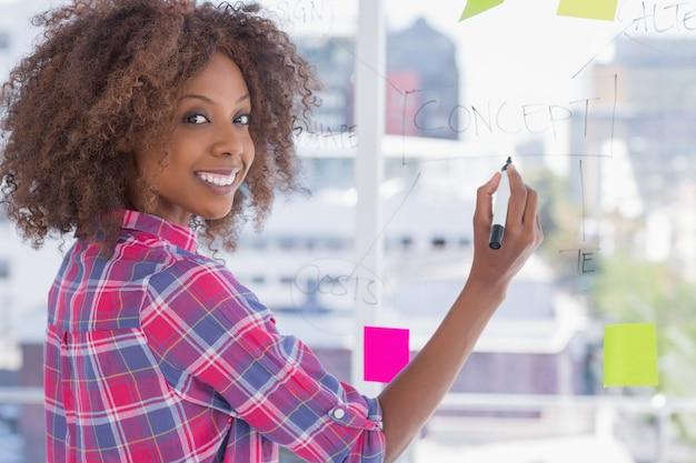 Mujer dibujando en diagrama de flujo con notas adhesivas y sonriendo a la cámara