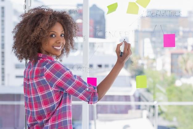 Mujer dibujando en diagrama de flujo y sonriendo a la cámara