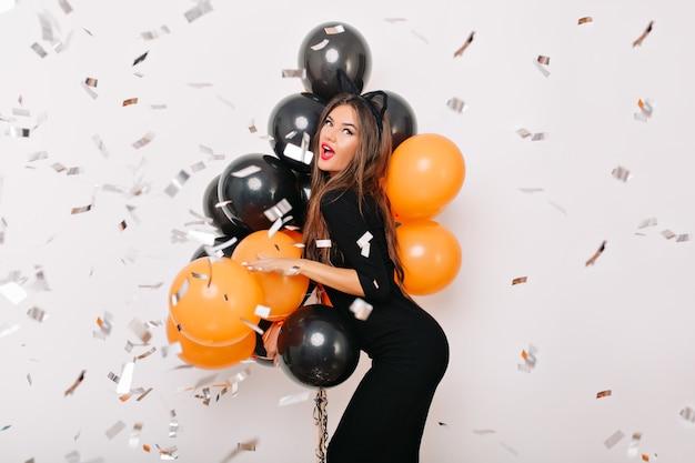 Mujer dichosa con cabello castaño bailando en la fiesta