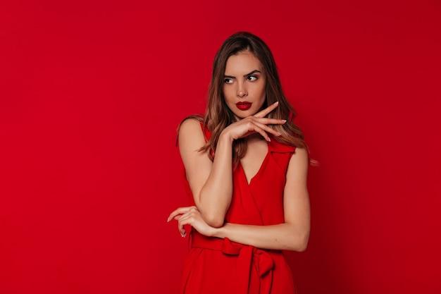 Mujer dichosa con maquillaje de noche con vestido rojo posando sobre pared roja
