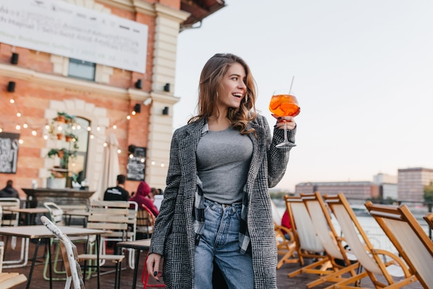 Mujer dichosa en traje casual levantando copa con cóctel de naranja en el fondo de la ciudad