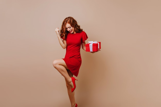 Mujer dichosa en zapatos de tacón bailando en la fiesta de navidad. feliz cumpleañera expresando felicidad.