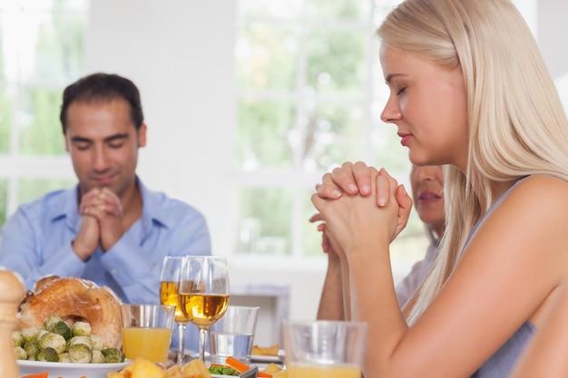 Mujer diciendo gracia con la familia antes de la cena