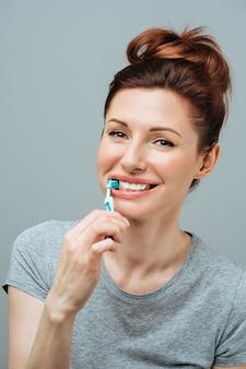 Mujer con dientes blancos sanos sostiene un cepillo de dientes y sonríe concepto de higiene bucal