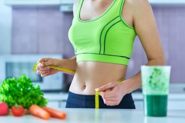 Mujer de dieta en ropa deportiva con cinta métrica y un batido verde para perder peso.