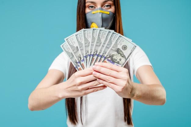 Mujer con dinero en dólares con máscara de respirador