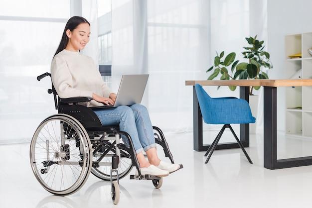 Mujer discapacitada joven que se sienta en una silla de ruedas usando el ordenador portátil en el lugar de trabajo