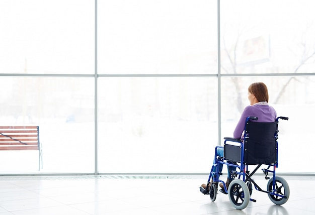 Mujer discapacitada mirando la ventana