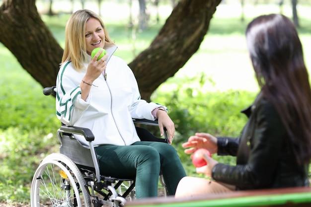 Mujer discapacitada en silla de ruedas comiendo manzana con su amiga en el parque rehabilitación de discapacitados