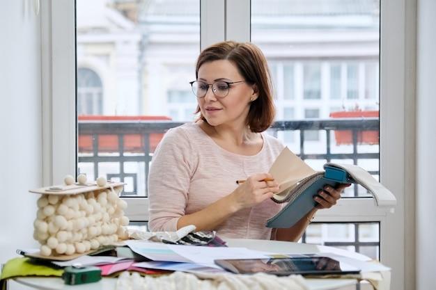 Mujer diseñadora de interiores trabajando en la mesa en la oficina con muestras de telas decorativas de interiores para cortinas