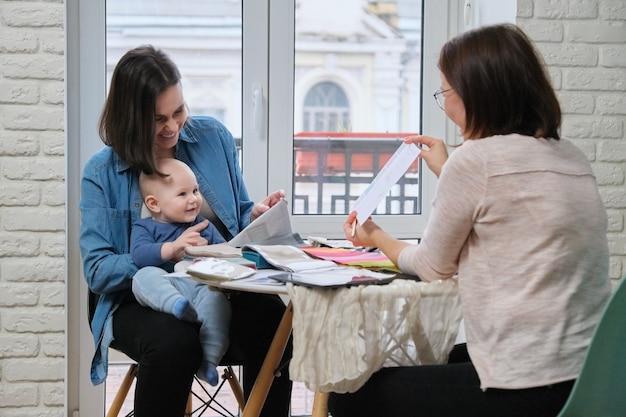 Mujer diseñadora textil y joven madre con bebé eligiendo telas para cortinas, almohadas, colchas, tapicería
