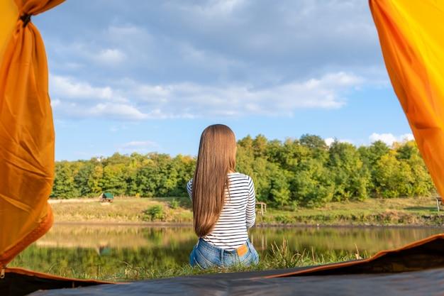 Mujer disfruta de la naturaleza frente a la carpa
