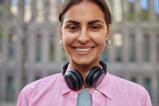 La mujer disfruta de su tiempo libre pasa el fin de semana con amigos paseos en la ciudad escucha música feliz por el examen aprobado con éxito sonríe ampliamente plantea en borrosa