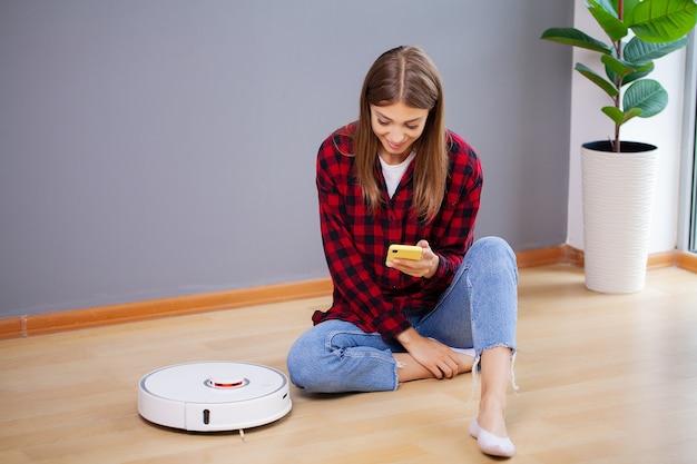 La mujer disfruta del trabajo de un robot aspirador inteligente.