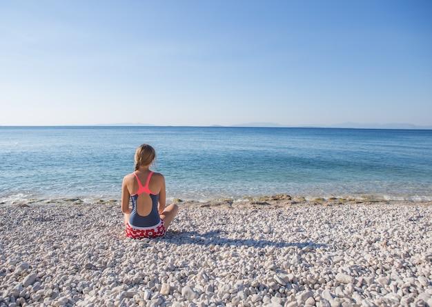Mujer disfruta de vacaciones tropicales. descansando relajándose en la playa cerca del mar. grecia