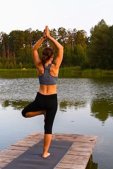 Una mujer disfruta de la vida salvaje en un lago. el concepto de aliviar el estrés en la naturaleza.