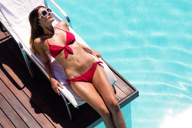 Mujer disfrutando de un baño de sol en el borde de la piscina