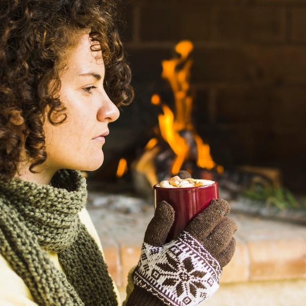 Mujer disfrutando de una bebida caliente cerca de la chimenea