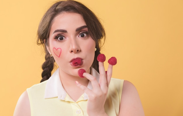Mujer disfrutando comiendo frambuesas fuera de sus dedos