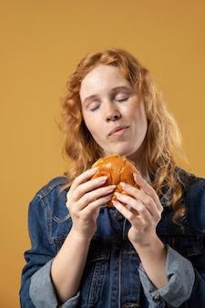 Mujer disfrutando comiendo una hamburguesa