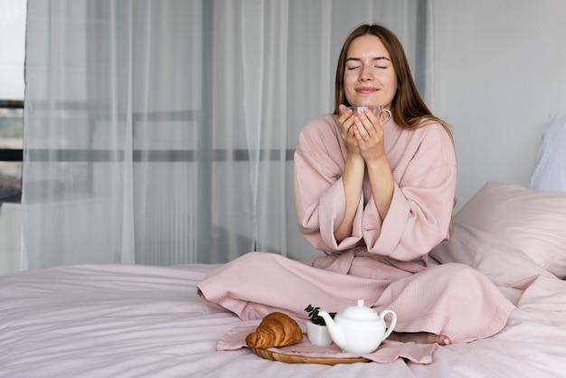 Mujer disfrutando el desayuno en la cama sola