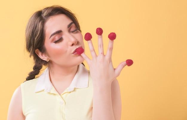Mujer disfrutando de las frambuesas en sus dedos con espacio de copia