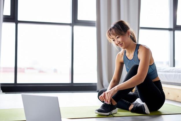 Mujer disfrutando de hacer ejercicio en la colchoneta sola en casa, descansar, usando la computadora portátil. mujer fuerte en ropa deportiva