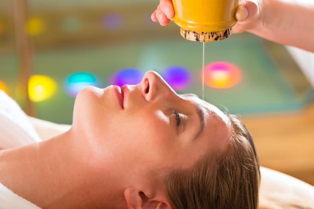 Mujer disfrutando de un masaje de aceite ayurveda