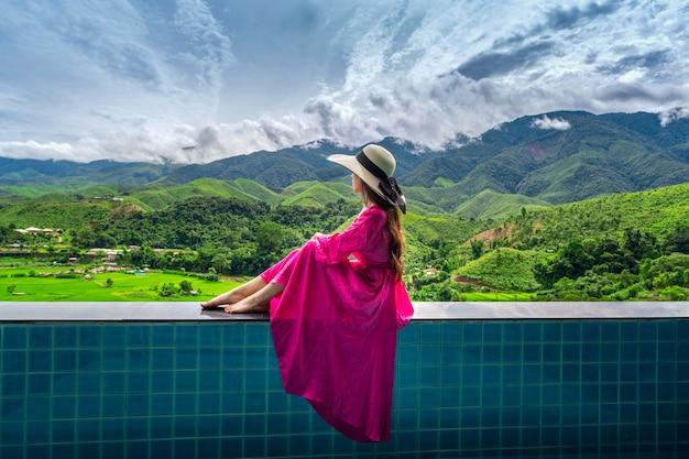 Mujer disfrutando del mirador de la terraza de arroz y el bosque verde en nan, tailandia