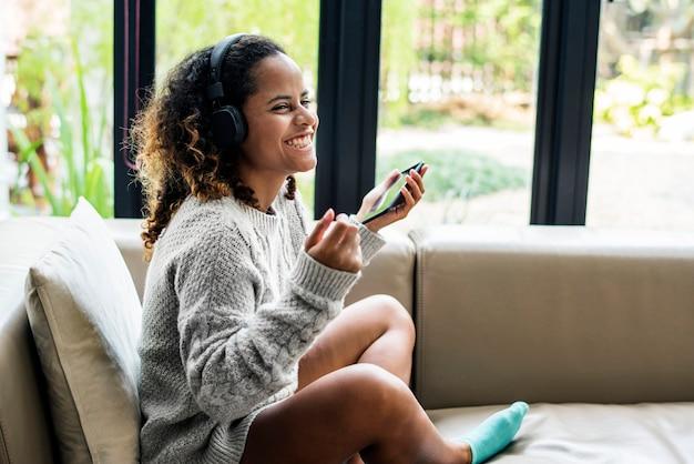 Mujer disfrutando de la música en su sofá