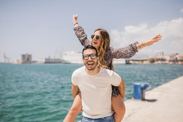 Mujer disfrutando de un paseo a cuestas en la espalda de su novio cerca del mar