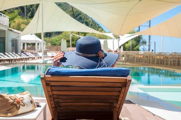 Mujer disfrutando y relajándose en la tumbona junto a la piscina
