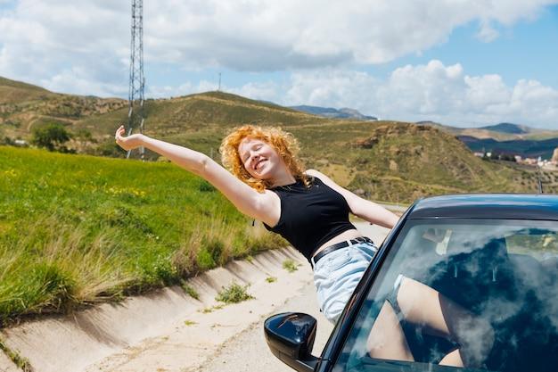 Mujer disfrutando de un viaje por la ventanilla del coche y estirando el brazo con los ojos cerrados