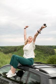 Mujer disfrutando de la vida mientras posa encima del coche