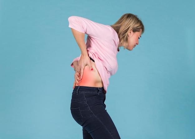 Mujer disgustada que sufre de dolor de espalda baja sobre fondo azul
