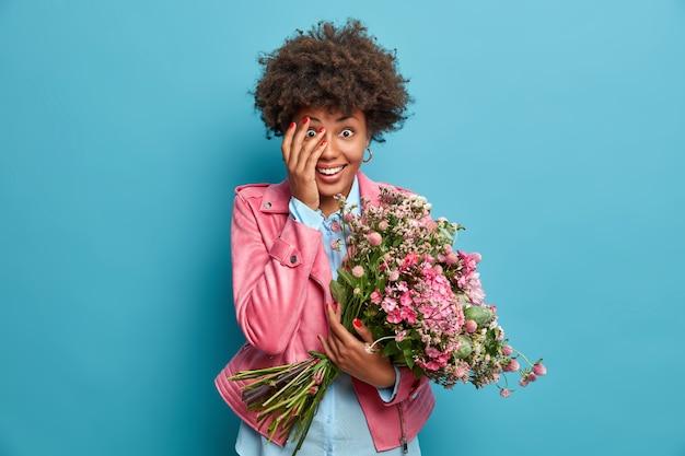 Mujer divertida alegre recibe una sorpresa agradable inesperada, sostiene un gran ramo de flores