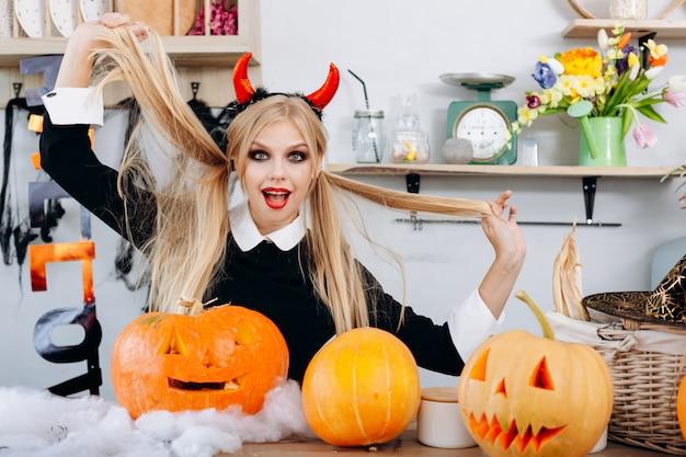 La mujer divertida del diablo que se sienta en la tabla al lado de una calabaza engaña alrededor. festividad de todos los santos