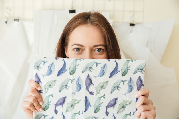 Mujer divertida escondida con telas estampadas