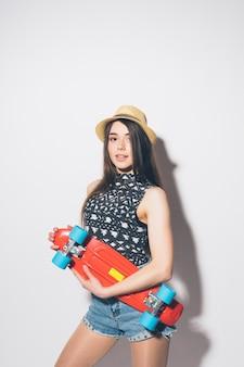 Mujer divertida hipster con longboard rosa aislado