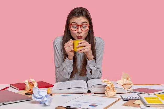 Mujer divertida mira sorprendentemente una taza de bebida caliente, toma un descanso para tomar café, estudia información en la enciclopedia, usa gafas transparentes y camisa