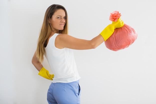 Mujer divertida mostrando cuánta basura está en bolsa