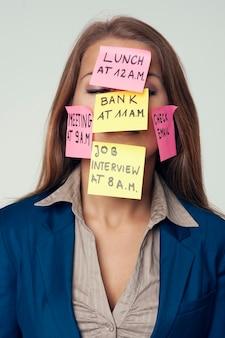 Mujer divertida con notas adhesivas en la cara. no olvides